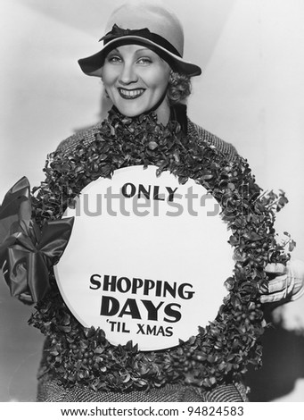 Woman with sign with number of shopping days until Christmas - stock photo