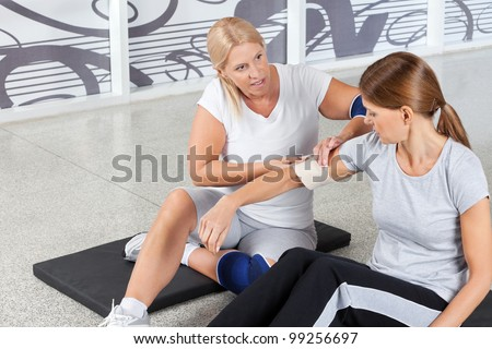 Woman with sports injury gets First Aid from fitness trainer in gym - stock photo