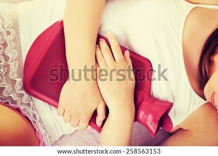 Woman with stomachache and hot water bag. - stock photo
