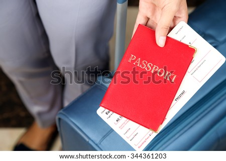 Woman with suitcase holding passport  and tickets close up - stock photo