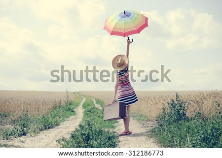 Woman with suitcase standing on road between field of wheat. Backview of girl in hat rising umbrella. - stock photo