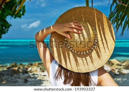 Woman with sun hat at tropical beach - stock photo