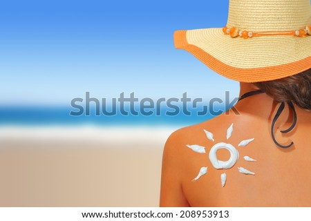 Woman with sun shaped sunscreen on her back - stock photo