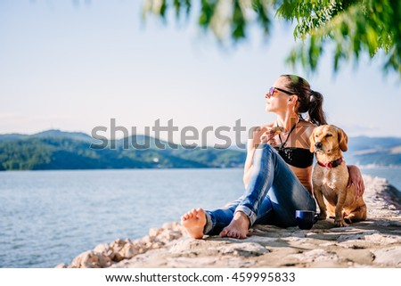 Woman with sunglasses wearing black bikini and jeans sitting on the beach with her small yellow dog - stock photo