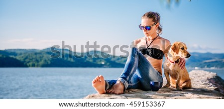 Woman with sunglasses wearing black bikini and jeans sitting on the stone dock with her small yellow dog - stock photo