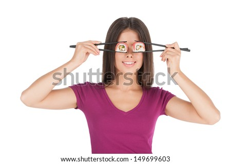 Woman with sushi. Beautiful mixed race woman holding sushi by chopsticks in front of her eyes while standing isolated on white - stock photo