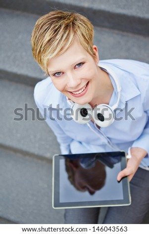 Woman with tablet computer and headphones sitting on stairs - stock photo