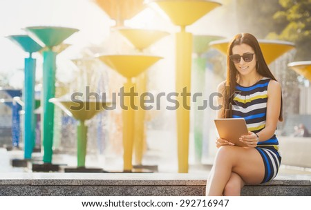 woman with tablet near fountain - stock photo