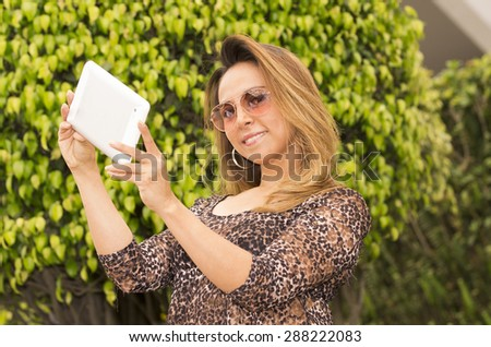 Woman with tablet outdoors wearing sunglasses posing for selfie - stock photo