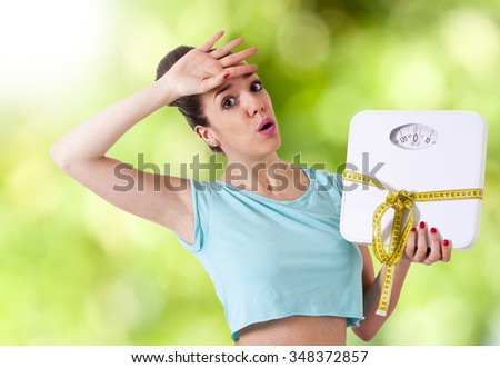 woman with tape measure worried about weight - stock photo