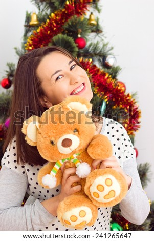 Woman with teddy bear  under the Christmas tree at room - stock photo