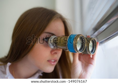 woman with the field-glass in hands observes the detective story through a window - stock photo