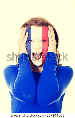 Woman with the French flag painted on her face. - stock photo