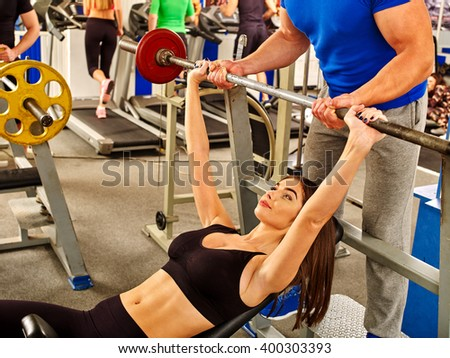 Woman with  thin waist working his arms and chest at gym. She lifting barbell. - stock photo