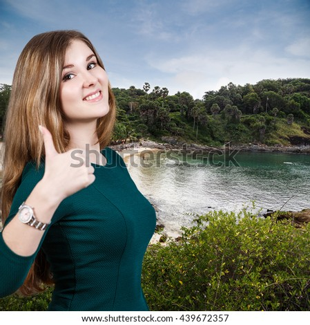 Woman with thumbs up on the beach baclground. - stock photo