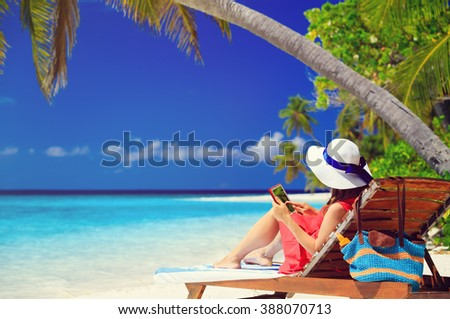 woman with touch pad on tropical beach - stock photo