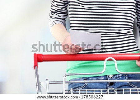 Woman with trolley in supermarket close-up - stock photo