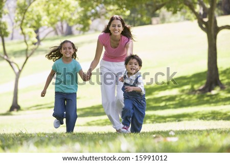 Woman with two young children running outdoors smiling - stock photo