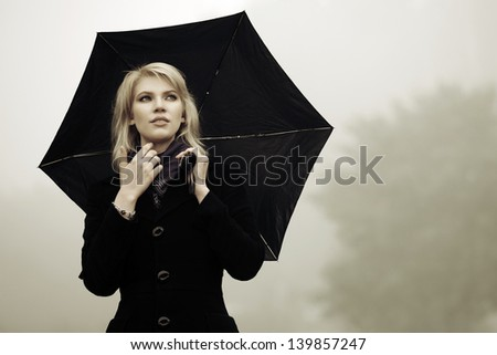 Woman with umbrella against a morning haze - stock photo