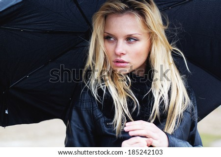 Woman with umbrella in rainy weather - stock photo