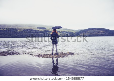Woman with umbrella standing in lake - stock photo