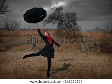 Woman with umbrella turning inside out by the wind - stock photo