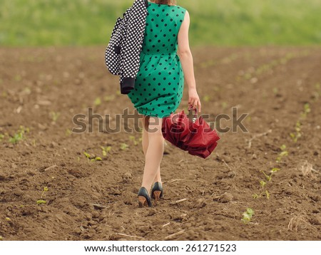 woman with umbrella walking in field after rain - stock photo