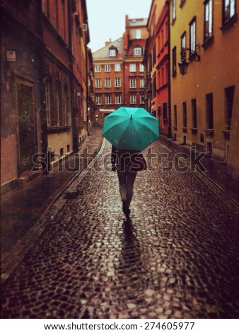 Woman with umbrella walking on the rain in old town of Warsaw, Poland. Vintage edited picture  - stock photo