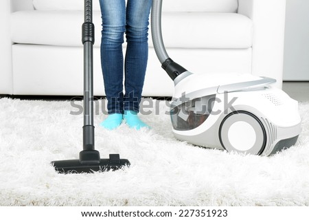 Woman with vacuum cleaner in room - stock photo