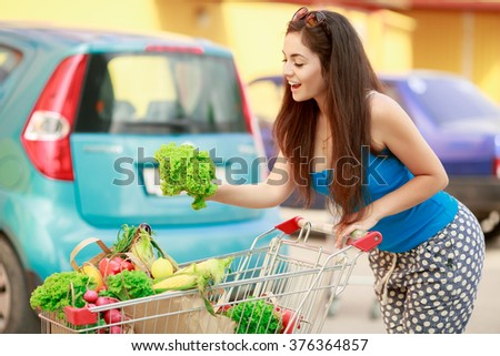 Woman with vegetables in shopping cart at grocery market. Girl after shopping in mall. Female with food in bags at supermarket, health eating food, trendy soft grain filter instagram like, series - stock photo