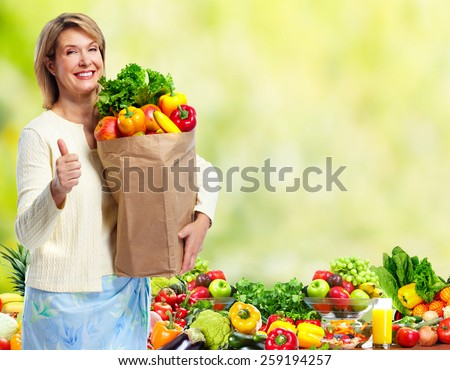 Woman with Vegetables over green background. Healthy diet. - stock photo