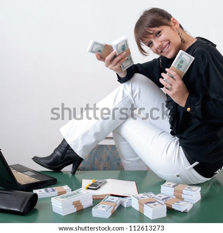 Woman with very excited look on her face holding money and sitting on desk at office. Packs of US dollars around her - stock photo