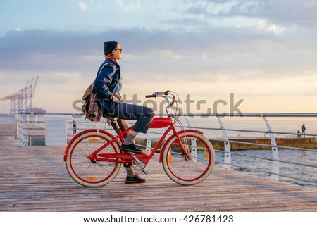 woman with vintage bicycle looking at view on seaside during sunset or sunrise - stock photo