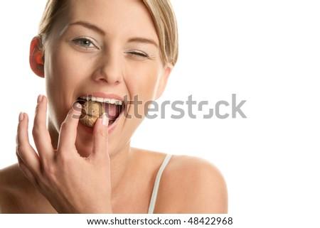 Woman with walnut winking - stock photo