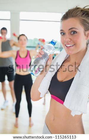 Woman with water and towel in aerobics class - stock photo