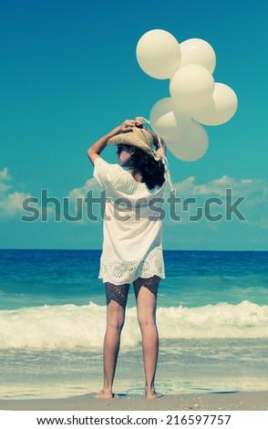 woman with white balloons on seaside - stock photo
