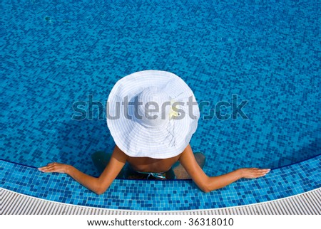 Woman with white hat relaxing in swimming pool in blue water - stock photo