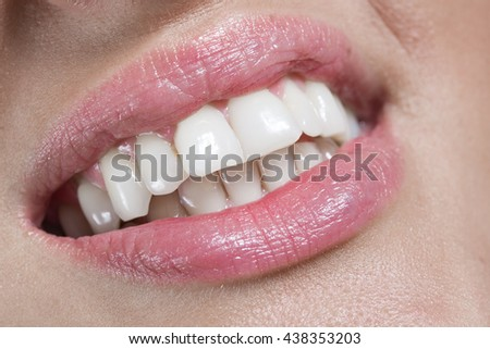 Woman with white teeth smiling, closeup of lips and teeth - stock photo