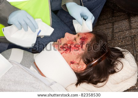 Woman with wounded face being helped by a paramedic - stock photo