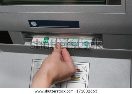 Woman withdrawing money from card at ATM - stock photo