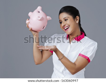 Woman withdrawing money from piggy bank - stock photo