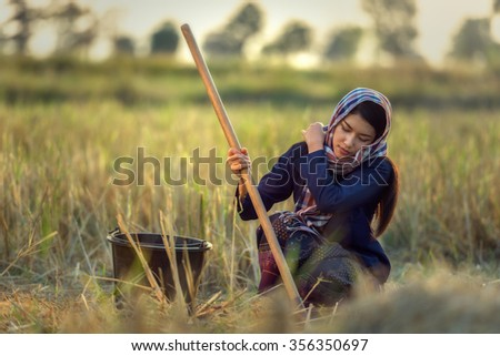 Woman worker in farmer suit on rice fields, Thailand (Vintage color) - stock photo