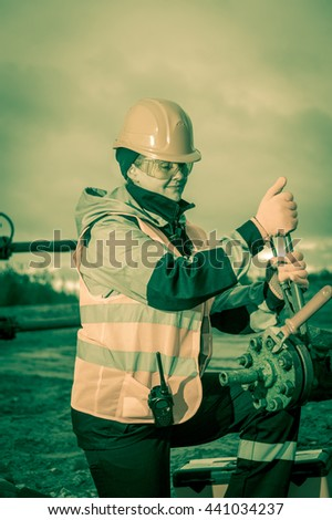 Woman worker on the oil field repairing of oil and gas well, with the wrench wearing  helmet and work clothes. Working process on oil wellhead. Toned sepia. - stock photo