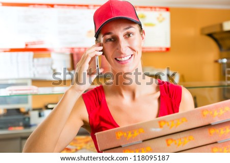 Woman working as delivery girl in a pizza place holding several pizza boxes smiling - stock photo