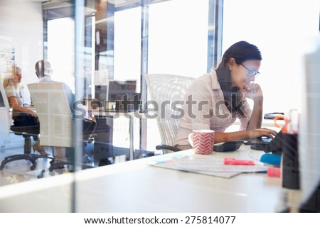Woman working at computer in an office - stock photo