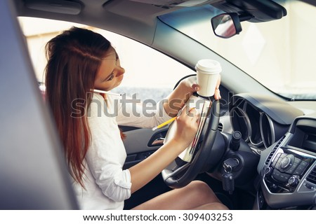 Woman working at the wheel in the car - stock photo