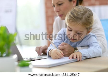 Woman working from home while daughter is drawing - stock photo