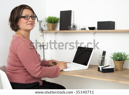 Woman working in a cozy workspace at home - stock photo
