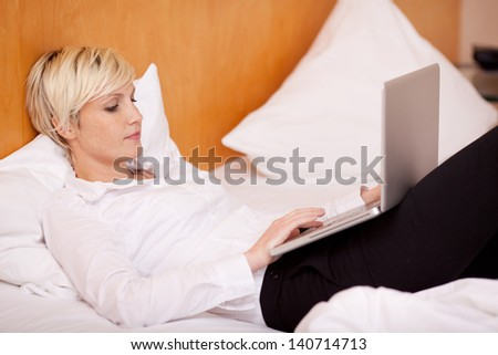 Woman working in hotel room on laptop - stock photo