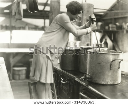 Woman working in soup kitchen - stock photo